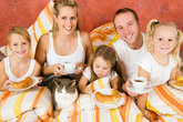 family with cat in bed at breakfast