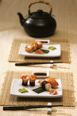 Close-up of sushi served in a tray with Asian teapot