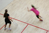 Two female squash players in fast action on a squash court (motion blurred, colo