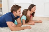 Happy Family Lying On Rug At Home