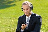 Businessman Listening Music In Park