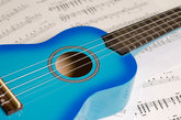 Blue guitar on a background of sheet music