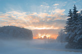 Winter morning snowy scenery with dawn sunlight rays breaking clouds