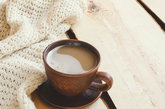 Soft white knitted sweater and cup of hot cocoa on an old wooden board. Cozy Christmas holidays at home.