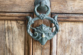 An antique pull handle knob on a vintage wooden door. Architecture in Valletta, Malta.
