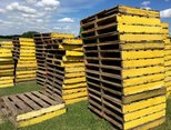 several piles of yellow wooden pallets for transporting turf on the field