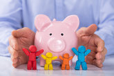 Hand Protecting The Piggybank With Colorful Family