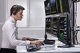 Stock Market Broker Analyzing Graphs On Computer Screens