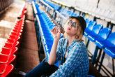 young slim woman dressed in blue checked shirt, cap and jeans, Will depart at dawn on summer day Sits spectator places of the fans Smokes a cigarette
