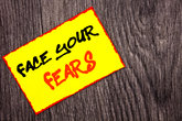 Conceptual hand writing text showing Face Your Fears. Concept meaning Challenge Fear Fourage Confidence Brave Bravery written on Yellow Sticky Note Paper on the wooden background.