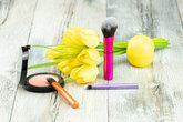 Decorative composition of cosmetics with yellow tulips on rustic bright wooden table. Concept card.