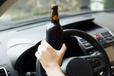 Transportation and vehicle concept - woman drinking alcohol while driving the car