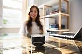 Woman Listening To Music On Wireless Speaker