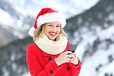 Woman on christmas holidays using phone looking at you