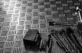 Tools on industrial metal checker plate. Metal checkerplate for anti skid. Wrench, and hex key on metal sheet floor. Silver bump ground with art pattern. Silver texture background.