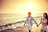 happy asian young couple walking on the beach at sunset
