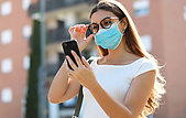 City lifestyle stylish hipster girl with surgical mask reading a message on mobile phone in street
